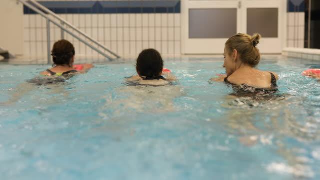 Rijpe vrouwen die houden van drijvers tijdens het zwemmen in zwembad