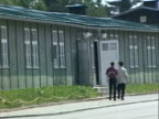 / Mauthausen concentration camp exterior of barracks couple walks by