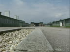 Mauthausen concentration camp wide road with barracks camp entrance and exterior walls topped with barbed wire