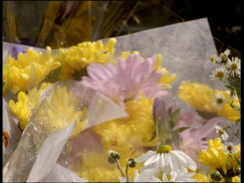 Mauve and yellow flowers in cellophane are added to other memorial flowers