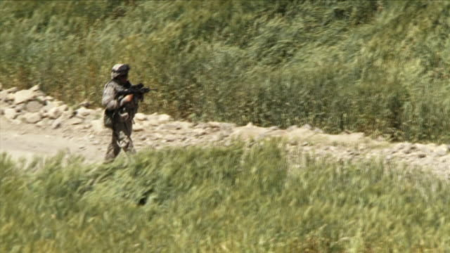 May 1 2009 WS ZO HA American soldier and local child walking down dirt road / Najil Afghanistan