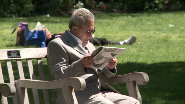 May 13 2010 MS Reader sitting on park bench with newspaper / Pennsylvania United States