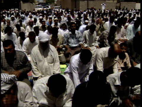May 8 1999 PAN Muslim men and boys greeting each other while kneeling in prayer / Basra Iraq