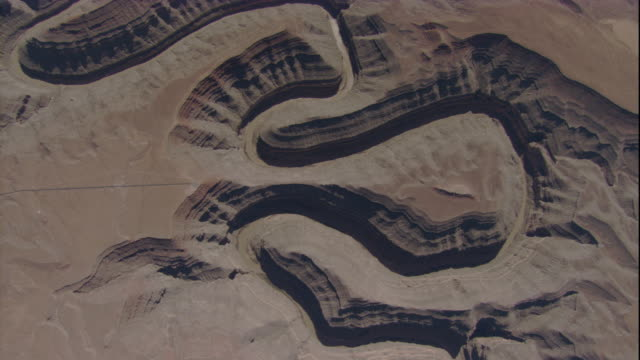 A meandering river flows through a canyon in the desert. Available in HD.