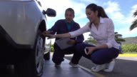 Mechanic assistance arriving to help a woman with a flat tire