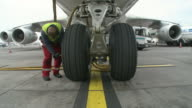 MS TU Mechanic checking airplane tyre / Findel-Airport, Luxembourg, Luxembourg-City, Luxembourg