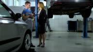 Mechaniker, die eine Checkliste Auto reparieren