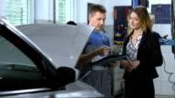 Mechanic Explaining Repairs For Car Repair
