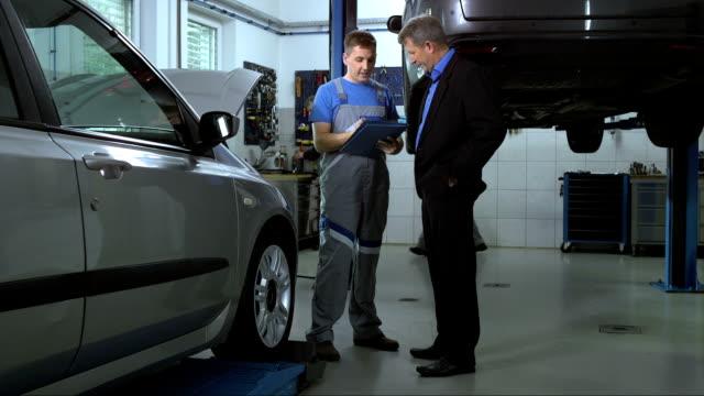Mechanic Explaining Repairs To Customer