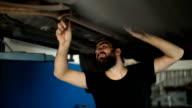 Mechanic man examining car