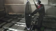 A mechanic moves a saw blade into position in a mill.