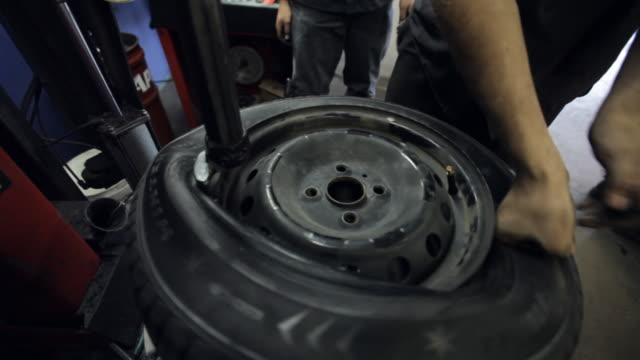 Mechanic puts tire on car wheel