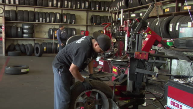 MS Mechanic removes flat tire off rim with machine / Los Angeles, California, USA