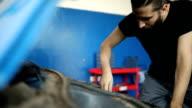 Mechanic repairing motor vehicle