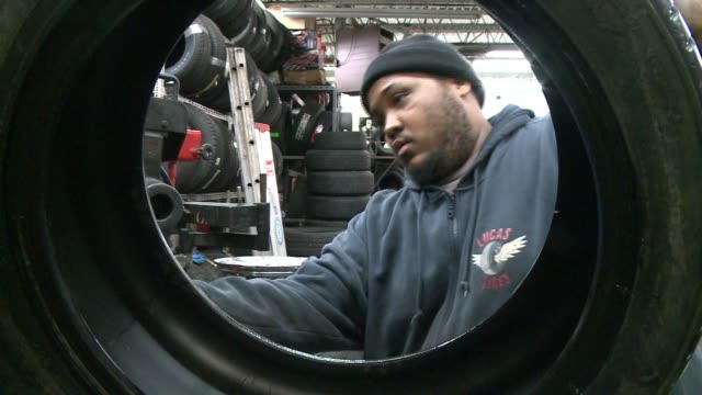 WGN Mechanic repairing tires in auto shop on February 24 2014 in Chicago Illinois