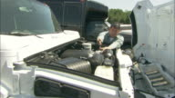 A mechanic uses a wrench on a vehicle and closes the hood.