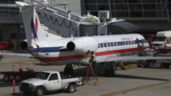 ZI mechanic works on American Eagle commuter jet (Embrear ERJ) parked at gate/DFW International Airport, Dallas-Fort Worth, Texas, USA