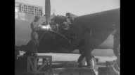 MS mechanics assemble US prop warplane engine / LS assembled planes lined up mechanics in left of screen / MS low angle of mechanics working on...