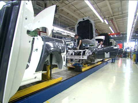 Mechanics work on cars that slowly move along automated production line Bremen