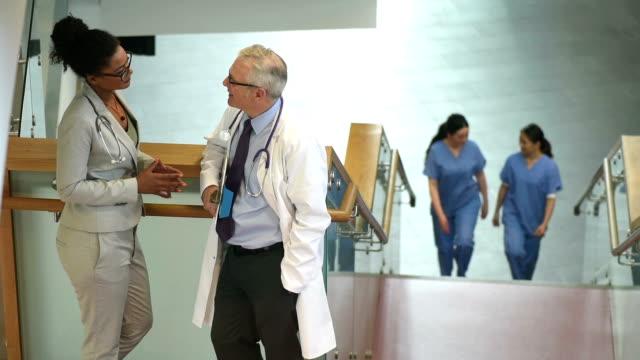 medische collega's chatten in een trappenhuis van een ziekenhuis
