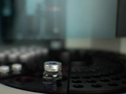 CU, SELECTIVE FOCUS, Medical samples in bottles rotating on platform