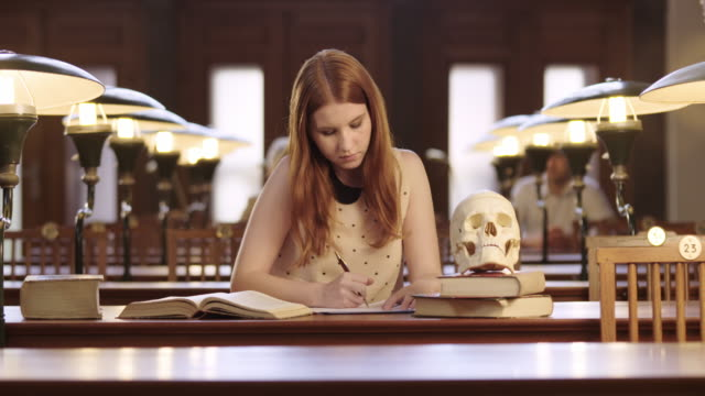 DS Medical student studying by observing a skull model in the library