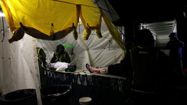MEDIUM PAN medical team helps injured people in tent - members of US Marines and FDNY take part in joint drill aimed at strenghting preparedness for chemical and biological attacks at Barclays Center