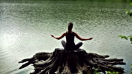 Meditating girl in the lake. Back view