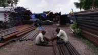 Medium and close shot workers use a metal hack saw to cut a iron pipe at a wholesale steel and iron market in Mumbai India Close shot workers feet in...
