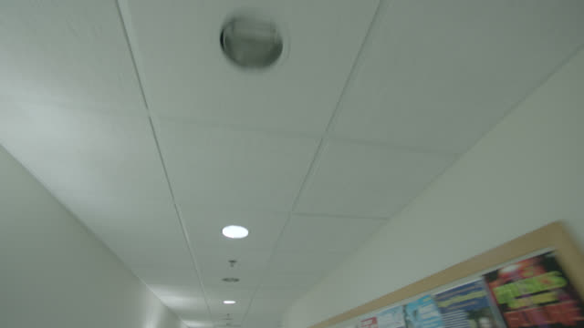 medium angle moving pov of hallway ceiling. could be in hospital. exit sign.