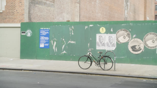 medium angle of artwork on wall. posters visible. bicycle parked on rack. pedestrians.
