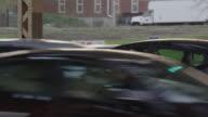 medium angle of cars on city street in near collision.