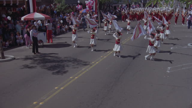 medium angle of parade. band with banner that reads fountain valley high school marches forward, wearing red uniforms. colorguard walks forward, then band follows, then float that reads our queen and court.