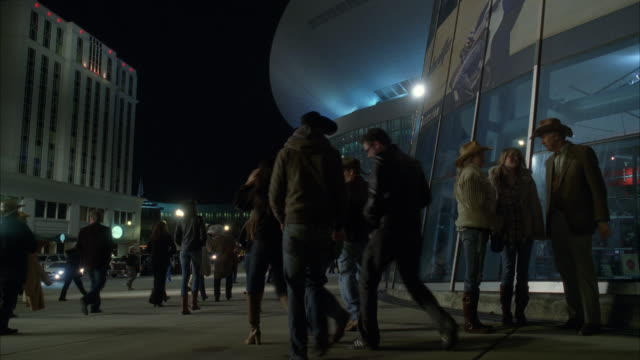 medium angle of people walking around courtyard of nashville convention center. men and women with cowboy boots and hats visible. could by country music concert.
