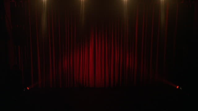 medium angle of red velvet curtains. could be in theater or on stage.