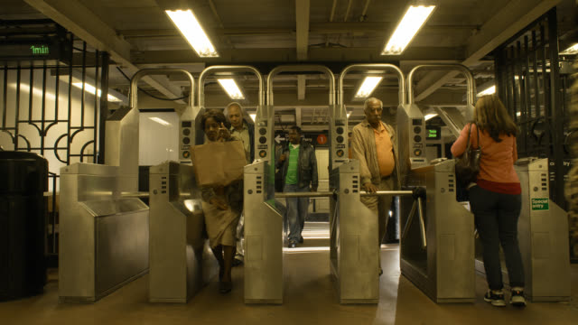medium angle of subway station entrance. commuters enter and exit through turnstiles.