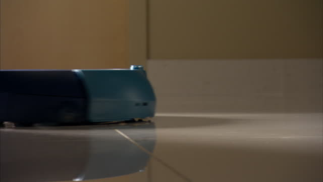 Medium Close Up pan-right - A small robotic vacuum cleaner moves along a tile floor.