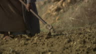 Medium Close Up pan-right - A woman uses a hoe and digs through the soil. / Tunisia