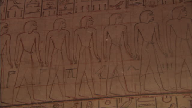 Medium Close Up, pan-right tilt-down - A mural depicts Egyptian figures and hieroglyphics / Egypt