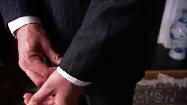 Medium Close Up static - A man wearing a pinstripe suit adjusts his cuffs. / London, England