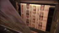 Medium Close Up static - Long sheets of printed paper run through a printing press /  Wisconsin, United States