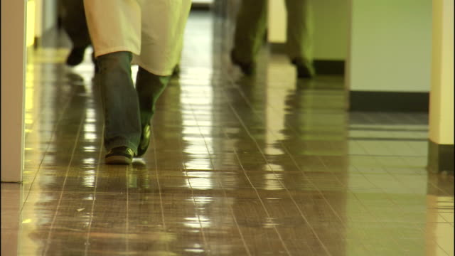 Medium Close Up static , Men walk along a reflective floor in a hallway. / California