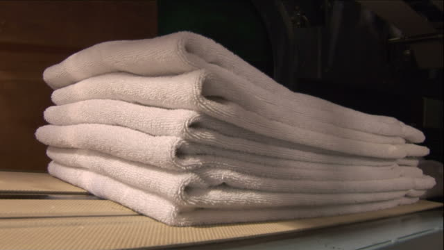 Medium Close Up steadicam - Folded white towels drop onto a stack below in a laundry / Las Vegas, Nevada