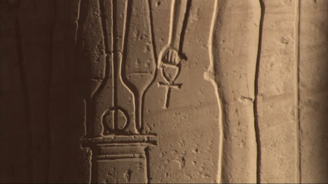Medium Close Up, tilt-up - A wall contains ancient Egyptian drawings and hieroglyphics