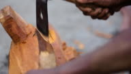 Medium closeup of man using Adze, or axe-like tool, to carve wood