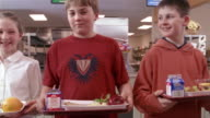 Medium dolly shot of children in school lunch line looking at camera/ Goram, Maine