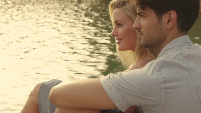 Medium dolly shot of couple sitting on dock beside lake/Marbella region, Spain
