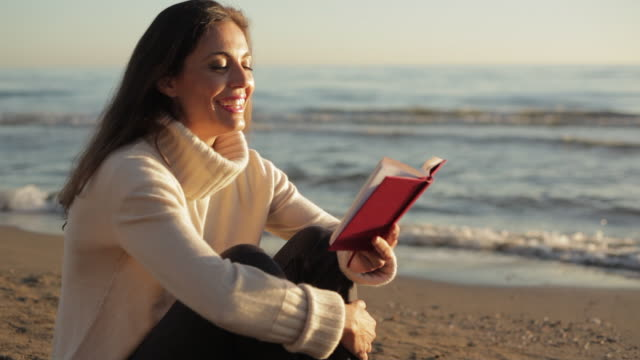 Medium dolly shot of woman reading book at the beach/Marbella region, Spain