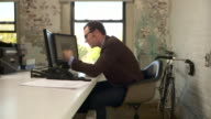 Medium full shot. Camera pushes in on profile of man at desk. He faces screen left. He is disappointed with what he sees on the computer screen and consequently bangs his head on the desk.