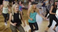Medium high angle panning shot of people dancing in exercise class / Orem, Utah, United States